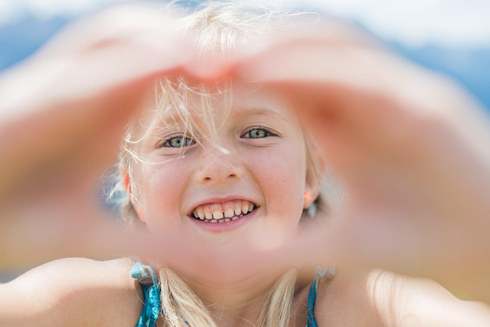 Ein kleines Mädchen streckt beide Hände zu einem Herz geformt in die Kamera.