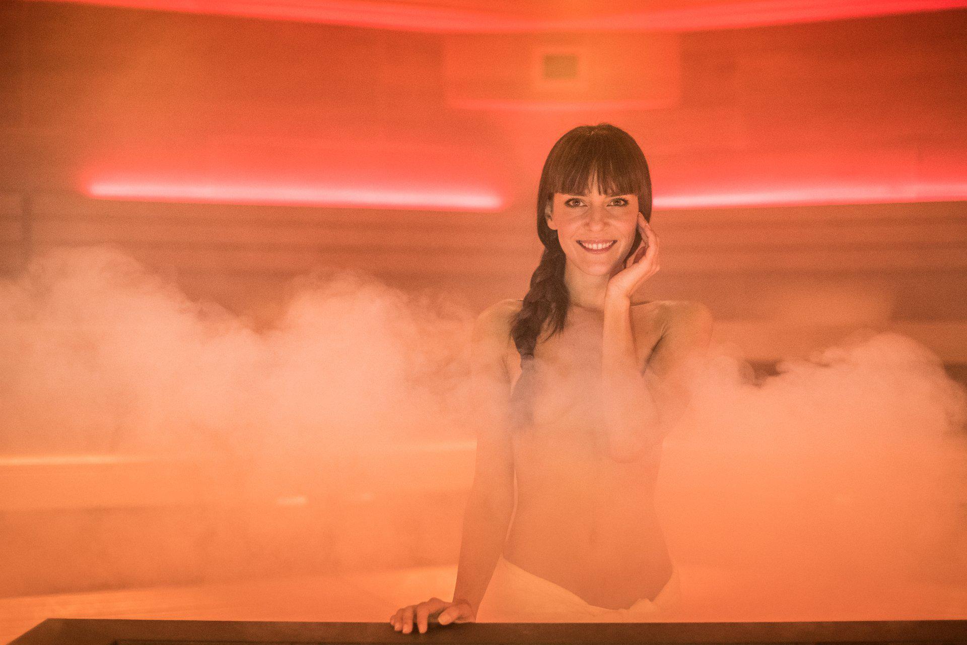Eine Frau in der Saune vom Rauch umhüllt und mit einem Handtuch bedeckt.