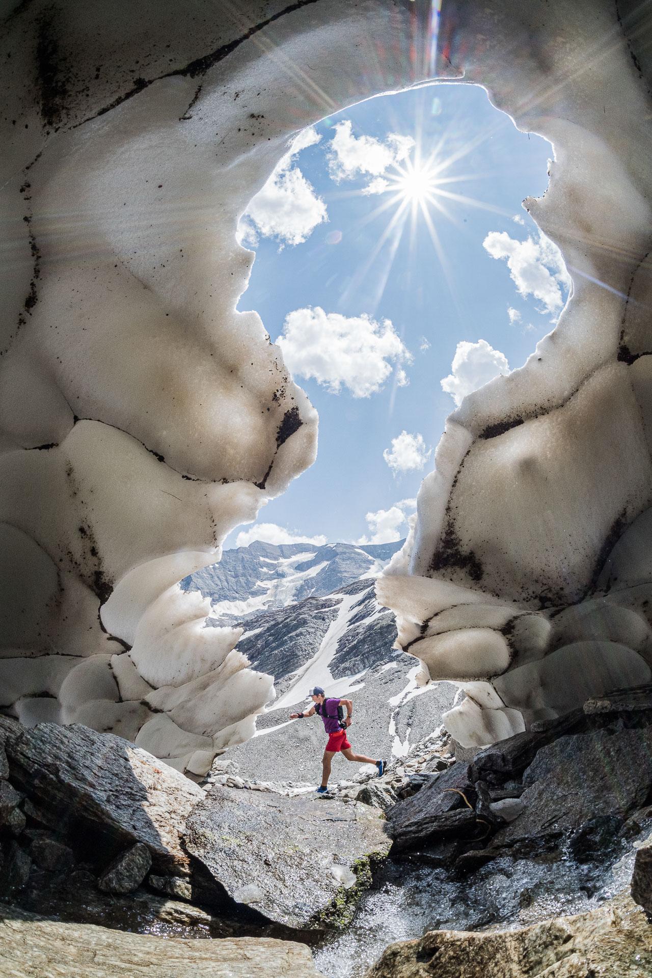 Ein Trailrunner unterwegs bei Schnee und Eis in den Bergen.