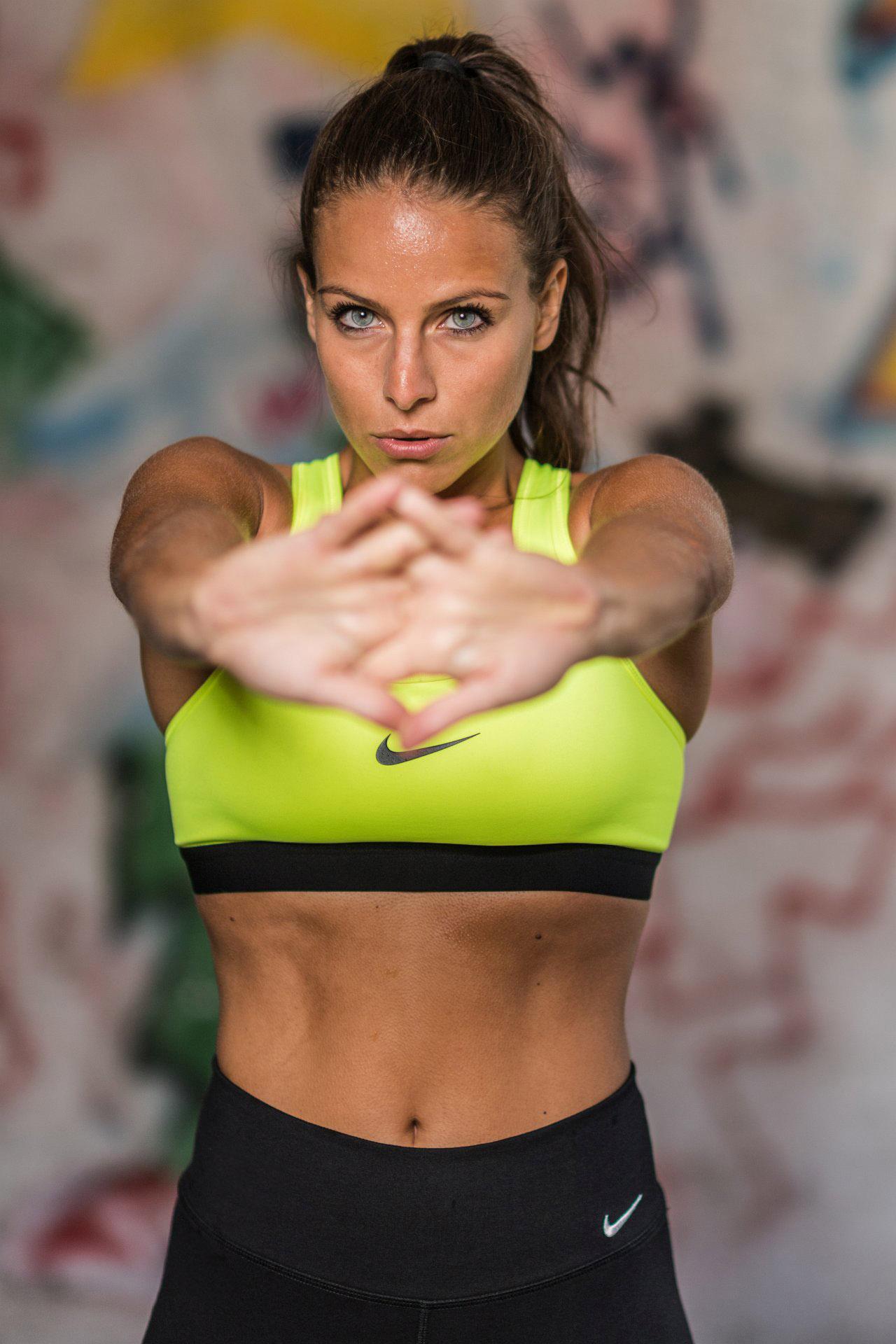 Frau in einem gelben Nike Outfit beim Dehnen.